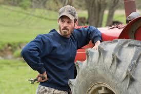 Suave Scoot McNairy, casually leaning against a tractor wheel.