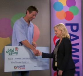 In this horribly low-resolution image, Detlef Schrempf (played by Detlef Schrempf) gives a Detlef-sized check to Leslie Knope (played by Amy Poehler).