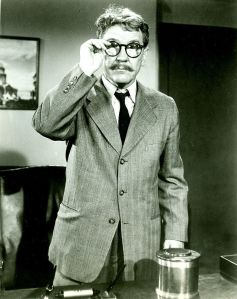 Burgess looking bookish as Henry Bemis.